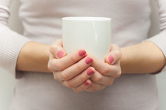Kvinnan räcker den hållande vita kopp te eller coffe Royaltyfri Bild