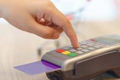 Kvinnan räcker den skrivande in koden för att betala via kreditkort - shopping royaltyfri fotografi