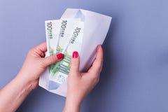 Kvinnan räcker det hållande kuvertet med kassa euroen bemärker reflexion royaltyfri foto
