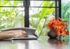 Kvinnan räcker genom att använda en bärbar dator hemma i dagtid Arkivfoto