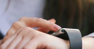 Kvinnan räcker genom att använda hennes smartwatchpekskärm, ilar meddelande för klockacloseup 4k lager videofilmer