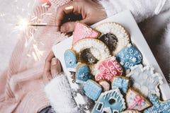 Kvinnan räcker håll en vit platta med dekorerade vinter-/julkakor och en gnistrande arkivbilder
