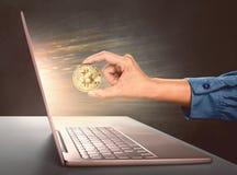 Kvinnan räcker hållande guld- bitcoin som är främst av en bärbar dator Royaltyfria Bilder