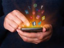 Kvinnan räcker hållande och att använda smartphonemobiltelefonen som kontrollerar sociala massmedianätverksapps Arkivfoto