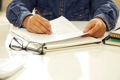 Kvinnan räcker handstilpapper i regeringsställning Arkivfoto