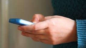 Kvinnan räcker handstilsmsmeddelandet på blåtttelefonen stock video