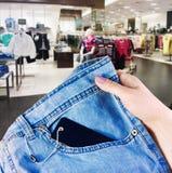 Räcka innehav som ett nytt parar av jeans på bakgrunden av ett supermar Royaltyfria Bilder