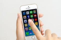 Kvinnan räcker innehavet och att trycka på en Apple iPhone 5s Royaltyfri Foto