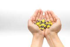 Kvinnan räcker innehavgruppen av guling, och grå färger capsule mediciner Arkivfoton