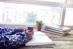 Kvinnan räcker läseboken med kaffe Arkivbilder