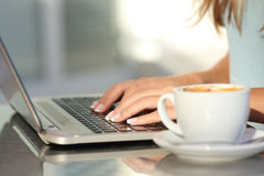 Kvinnan räcker maskinskrivning i en bärbar dator i en coffee shop Royaltyfria Bilder