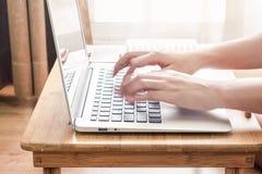 Kvinnan räcker maskinskrivning på bärbar datortangentbord Arkivfoto