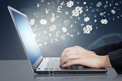 Kvinnan räcker maskinskrivning på bärbara datorn med valutasymboler Arkivfoto