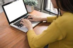 Kvinnan räcker maskinskrivningbärbar datordatoren med den tomma skärmen på tabellen i coffee shop Tom bärbar datorskärmåtlöje upp arkivfoto