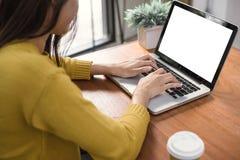 Kvinnan räcker maskinskrivningbärbar datordatoren med den tomma skärmen på tabellen i coffee shop Tom bärbar datorskärmåtlöje upp royaltyfri foto