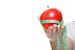 Kvinnan räcker med det röda äpplet och mäter tejpar isolerat Arkivbilder