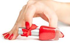Kvinnan räcker med en buteljera av rött spikar polskt Arkivbild
