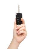 Kvinnan räcker på den nyckel- isolerade hållande bilen för bakgrund Royaltyfri Bild