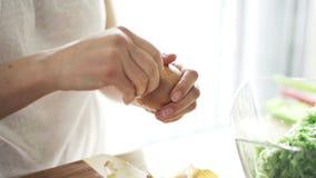 Kvinnan räcker skalningslöken i kök stock video