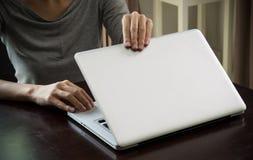 Kvinnan räcker tätt en bärbar dator hemma i hand för dagtidfokus Royaltyfri Foto