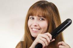 Kvinnan rätar ut hår det krullande järnet Arkivfoto