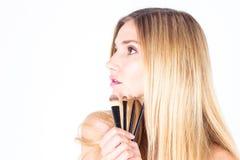 Kvinnan är hållande kosmetiska borstar Smink Arkivfoton