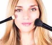 Kvinnan är hållande kosmetiska borstar Smink Royaltyfria Bilder