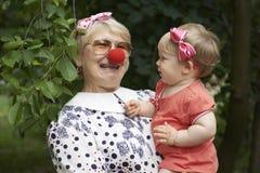Kvinnan är underhållande hennes lilla sondotter Arkivfoto