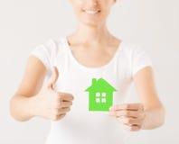 Kvinnan räcker det hållande gröna huset Royaltyfria Bilder