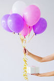Kvinnan räcker innehavgruppen av ballonger Arkivbilder