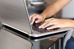 Kvinnan räcker maskinskrivning i en bärbar dator som hemma arbetar Arkivbild