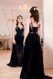 Kvinnan reflexion i spegel in snör åt länge klänningen fotografering för bildbyråer
