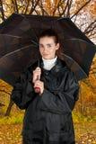 Kvinnan regnar in täcker Arkivbild
