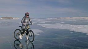 Kvinnan rider cykeln på isen Flickan är iklädd ett silvrigt klår upp ner och att cykla ryggsäcken och hjälmen Is av arkivfilmer