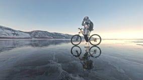 Kvinnan rider cykeln på isen Flickan är iklädd ett silvrigt klår upp ner och att cykla ryggsäcken och hjälmen Is av lager videofilmer