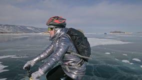 Kvinnan rider cykeln på isen Flickan är iklädd ett silvrigt klår upp ner och att cykla ryggsäcken och hjälmen Is av stock video