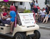Kvinnan rider i en golfvagn i Wellfleeten 4th Juli ståtar i Wellfleet, Massachusetts Arkivfoto