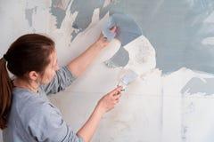 Kvinnan river av tapeten som tar bort tapeten från väggen med en spatel, processen av att uppdatera väggrumreparationen med royaltyfria bilder