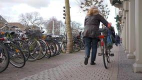 Kvinnan rullar cykeln ner stadsgatan förbi cykelparkering av ekologiskt ren transport för hyra för turister lager videofilmer
