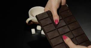 Kvinnan rymmer den svarta chokladst?ngen r royaltyfria bilder