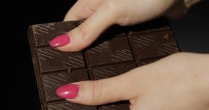 Kvinnan rymmer den svarta chokladst?ngen r arkivfoton