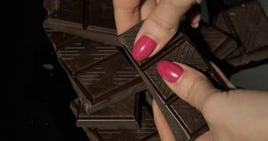 Kvinnan rymmer den svarta chokladst?ngen r arkivbilder