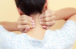 Kvinnan rymmer en hand på hals smärtar Arkivbild