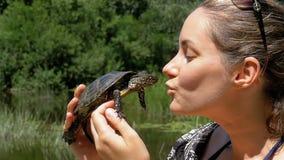 Kvinnan rymmer en liten flodsköldpadda i som henne, vänder mot händer nära på naturen långsam rörelse stock video