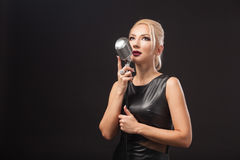Kvinnan rymmer en metallmikrofon arkivfoto
