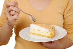 Kvinnan rymmer en platta med ett stycke av kakan Royaltyfri Bild