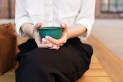 Kvinnan rymmer en smaragdbunke med grönt te för matcha i hennes händer över den gröna metalliska tabellen inomhus På tabellen fin royaltyfri fotografi