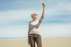 Kvinnan rymmer en smartphone och gör selfie Fotografering för Bildbyråer