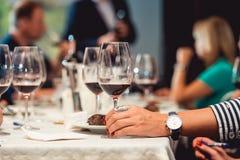 Kvinnan rymmer exponeringsglas av rött vin Folket betraktar färgen av vinet och försöket hur det luktar i olika exponeringsglas arkivbild