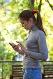 Kvinnan rymmer mobiltelefonen i hand Arkivbild